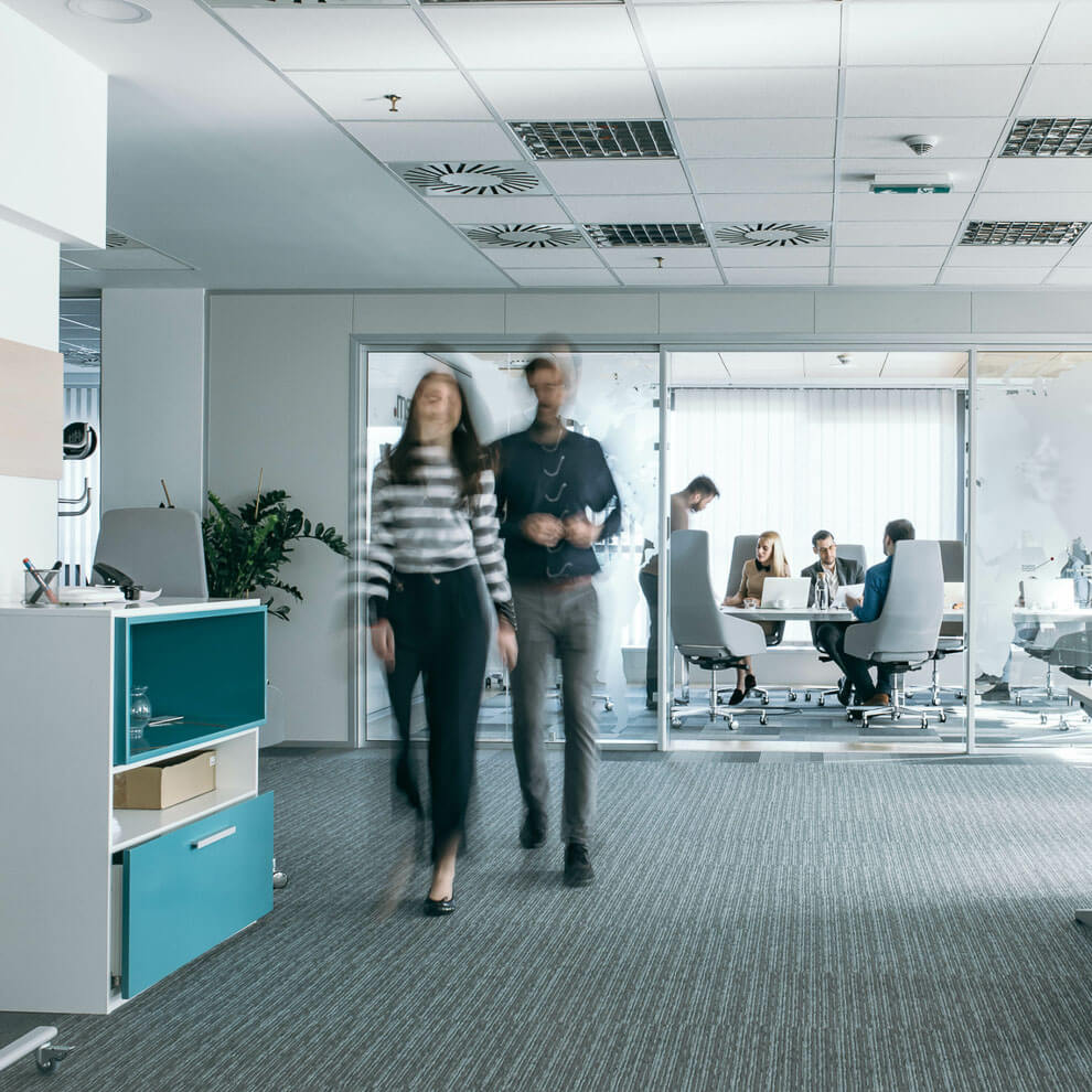 Blurred workers walking through an office